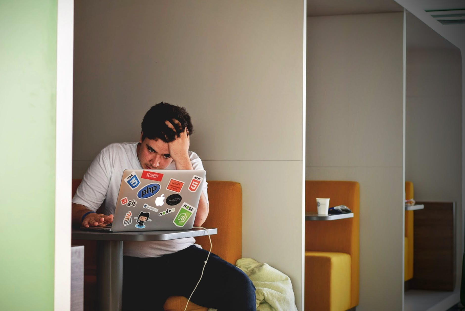 man in white shirt using macbook pro
