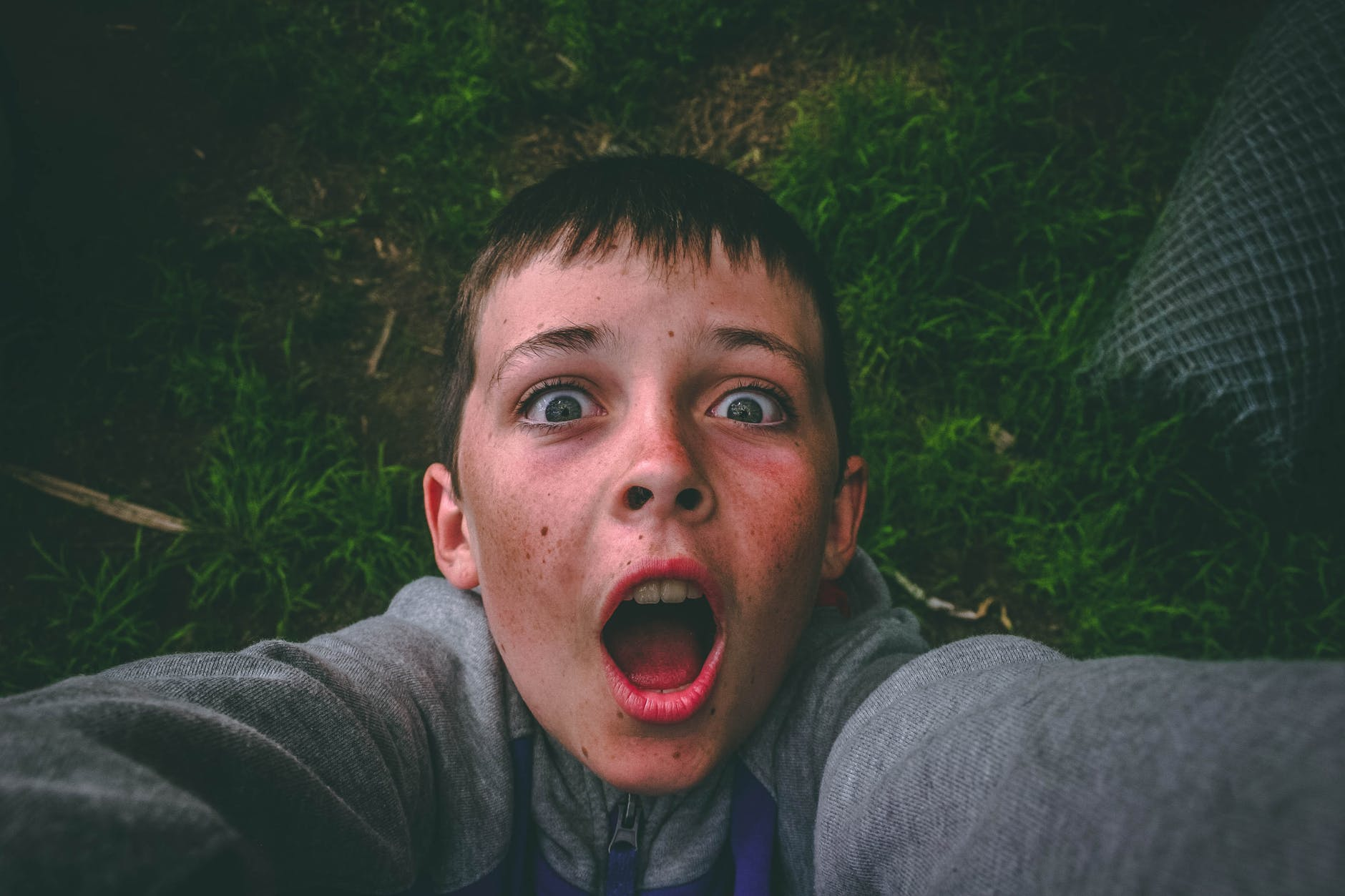 opened mouth black haired boy in gray full zip jacket standing on grass field taking selfie